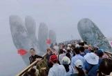Du khách leo xuống khu vực bàn tay khổng lồ ở cầu Vàng chụp ảnh